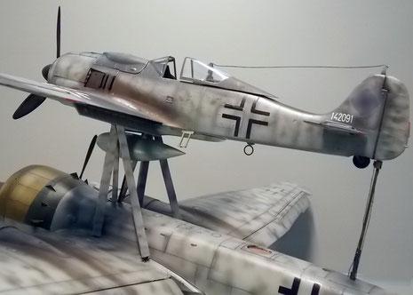 Die Focke-Wulf 190 mit Zusatztank unterm Rumpf steht auf dem absprengbaren Traggestell. Zwischen den Holmen verläuft eine Spritleitung zum Mutterflugzeug, um so die Reichweite des Steuerflugzeuges zu erhöhen.