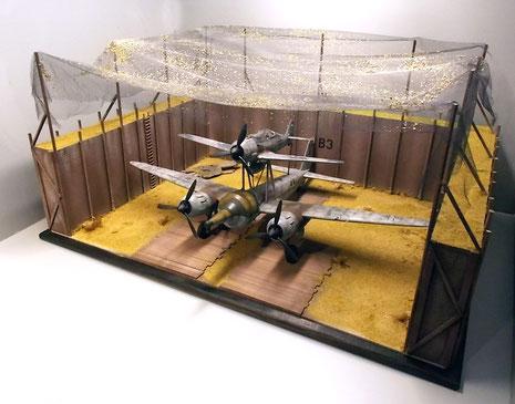 Seitenwände werden oben, sowie die Grundfläche um die Stellflächen mit Modellerde und Gras bedeckt. Die Holzelemente in zwei, drei Holzfarben gespritzt und trockenbemalt.