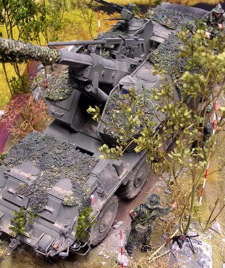 Mit der Tarnung durch die Besatzung verschwindet das große Fahrzeug fast im Gelände.
