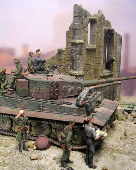 Grün-rostrote Tarnstreifen-unterbrochen von sandgelben, aufgespritzen Linien lassen die eckigen Konturen des Panzerkampfwagen VI verschwimmen.