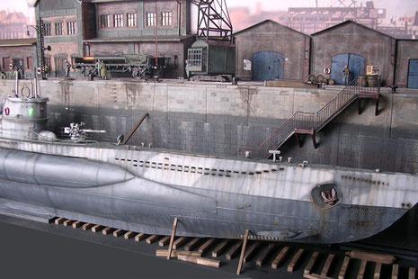 Das Boot ist im Trockendock auf hölzeneren Kiellagern abgelegt, stählerne Leitern führen vom Dockboden bis hinauf auf den Kai.