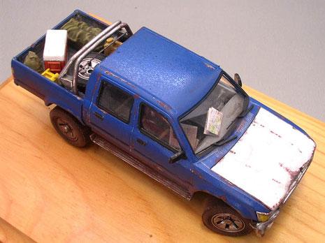 Das Fahrzeug wird ordentlich zerbeult und verrostet dargestellt. Logischerweise ohne die beigefügte MG-Lafette, schließlich handelt es sich um ein Zivilfahrzeug. Accessoires wie Karten unter der Frontscheibe helfen zum Realismus.
