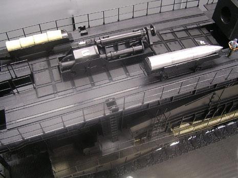 Ladetisch mit Dampfhydraulik, Treibladungen und Granate auf Munitionsschlitten