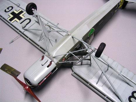 Unterseite in RLM-Hellblau zeigt Auspuffkrümmer und die Verstrebungen von Tragflächen und Fahrwerk.