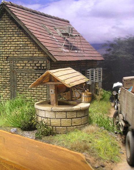 Der Ziehbrunnen vor dem Haus mit Holzbottich.