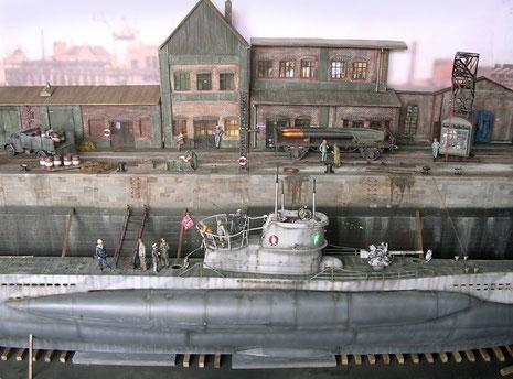 Auf drei Ebenen zeigt sich nebem dem Bootsmodell eine Dockstraße und eine Kulisse der typischen Hafengebäude eines französischen Hafens.