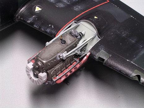 Motorgondel mit vorne dem hellgrauen Ölkühler, dahinter der gusseiserne Motorblock mit den seitlichen rostroten Auspuffkrümmern.