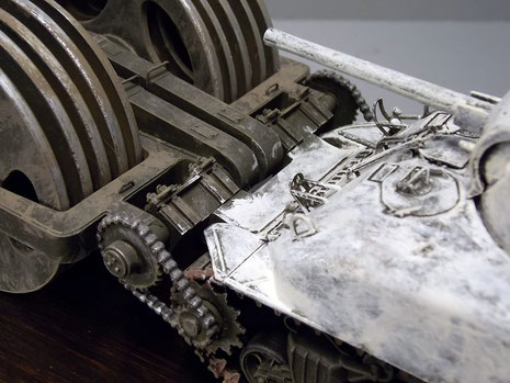 Das Kettenübersetzungsgetriebe, das die Laufrollen selber nochmal antreibt und mit dem Zahnkranzrad des Panzers verbunden ist.
