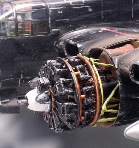 Linker, geöffneter Motor mit Aufhängung und Abgasrohren, sowie den 24 ringförmig angeordneten Zylindern.