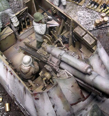 Blick in den Geschützraum mit Munitionskästen und der Richtmechanik des Geschützes.