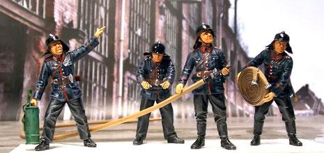 Die Viergruppe deutscher Feuerwehrmänner hat die entpsrechenden Posen für eine Löschaktion.
