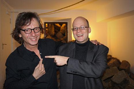 Purple Schulz (li) mit seinem Lichtpunkt und musikalischem Gruß an die Menschen. David Roth (re) als Veranstalter des Konzerts in Bergisch Gladbach.