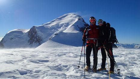 Pauline et Paul au sommet du Dôme du Gouter, avec une vue sur le vent rageur soufflant sur la partie sommitale du Mont-Blanc, nous privant du sommet ce jour-là. Une prochaine fois !