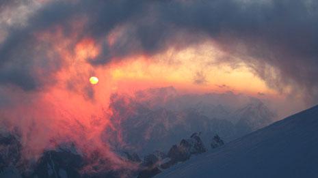 Irréel... Soleil et nuages au petit jour depuis l'arête des Bosses, peu avant le sommet du Mont-Blanc. Au fond, la pyramide du Weisshorn.