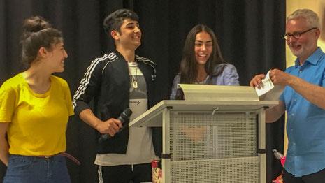 Drei Schülerinnen und Schüler der Sprachförderklassen halten im Anschluss daran eine kleine Abschiedsrede.