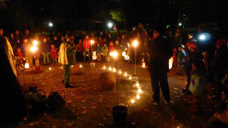 Personenhalbkreis markiert durch Kerzen und Fackeln beim Laternenspektakel im unteren Schlossgarten