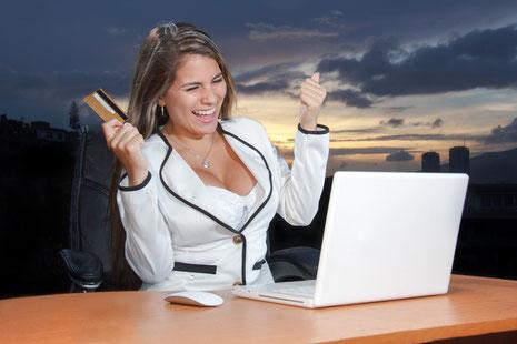 Eine Frau sitzt am Laptop und kauft mit Begeiserung ein. Sie hält weine Kreditkarte hoch und freut sich über ihren Einkauf.