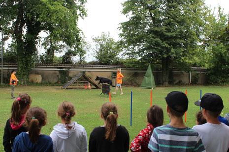 Gebannt verfolgten die Hockenheimer Ferienkinder die Vorführungen der Brühler Hundesportler. Hier zeigen Melanie Schwalbe (links mit Kappe) und Claudia Walter, wie Inola auf Kommando über ein Hindernis springt.