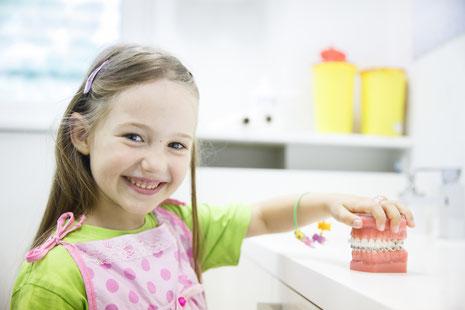 Zahnarzthelferin vor Computermonitor mit lachendem Kleinkind