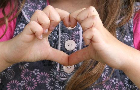 Les mains d'un enfant formant un coeur pour représenter la collection de créations solidaires de l'illustratrice Cloé Perrotin