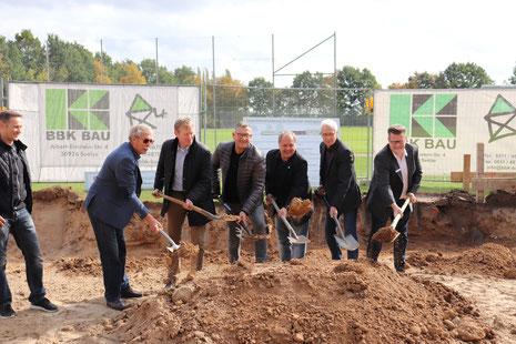 Architekt Marco Richard, Wilfried Petersen (stv. Vors. SV Arnum), Ulff Konze (Fraktionsvorsitzender CDU), Bürgermeister Claus Schacht, Ulf Meldau (Vors. Regionssportbund), Werner Schwertfeger (stv. Vors. SV Arnum) und Nils Wattenberg (Sparkasse)