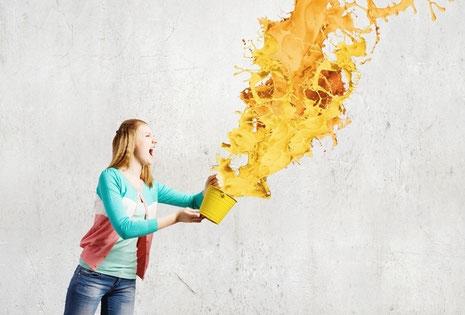 Mädchen vor grauer Wand schüttet einen Farbtoüpf mit oranger Farbe aus