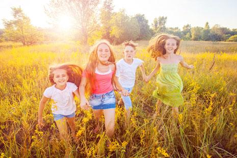 4 Kinder laufen über Wiese und halten sich an den Händen