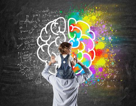 Vater mit Tochter auf den Schultern stehen vor einer Tafel, Zeichnung Gehirnhälften, rechte Gehirnhälfte bunt, linke Gehirnhälfte Zahlen