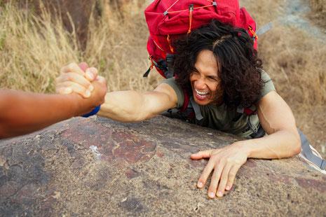 helping hand, Kletterer zieht sich an helfender Hand nach oben