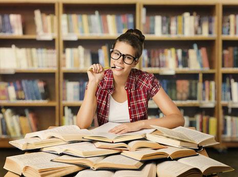 intelligent wirkende Studentin hat Bücher auf einem Schreibtisch ordentlich vor ihr liegen