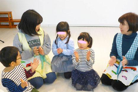 幼児教室の幼稚園児クラスのリトミックで、笑顔と穏やかな表情で生徒をサポートしています。