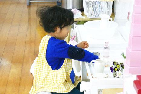 モンテッソーリの個別活動の時間に、日常生活の練習の生花の活動に2才児が集中して取り組んでいます。