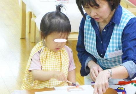 幼児教室のフィオーレコース(2歳児)のモンテッソーリ活動で生徒の活動を援助しています。