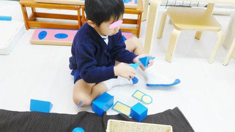 幼児教室のモンテッソーリ活動で幼稚園児が立体幾何のおしごとに自由な発想で取り組んでいます。