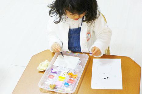 幼児教室の幼稚園児クラスで切り紙を選んで貼る貼り絵のお仕事に集中して取り組んでいます。