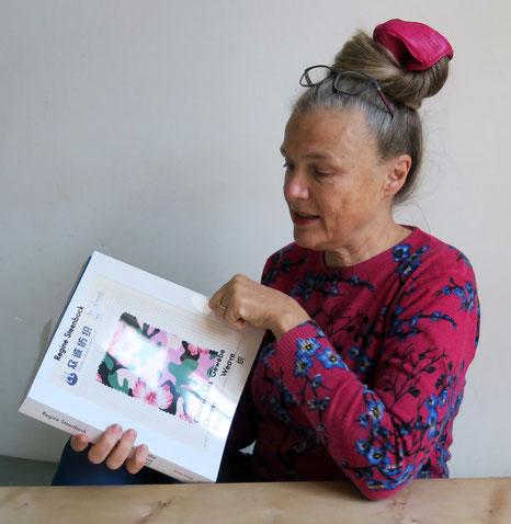 Eine Frau sitztend mit einem Buch in der Hand
