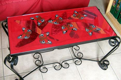 Table basse restaurée main : tissu rouge avec feuilles en tissu bariolé rouge, papillons en bois peints et vitre en verre par dessus.