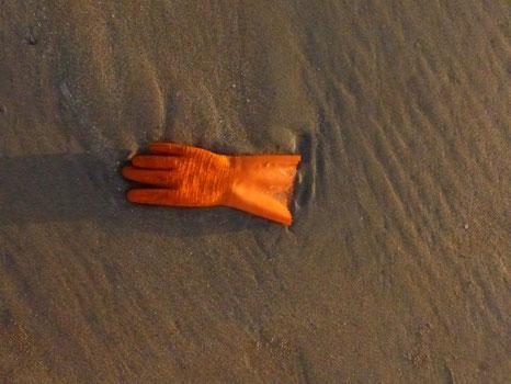 orangener Gummihandschuh liegt am Strand