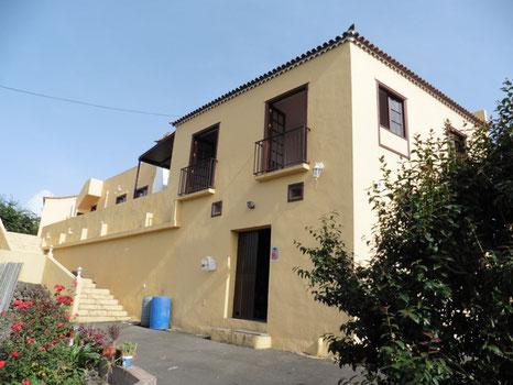 Kanarisches Wohnhaus mit 2 Etagen in beige gestrichen und die Fenster sind in dunkelbraun gehalten.