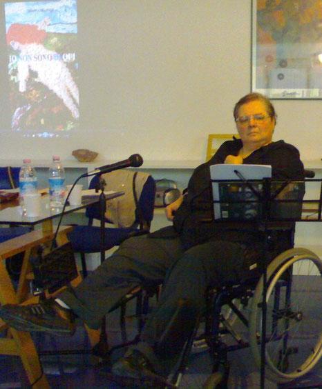 nella foto io alla presentazione del mio libro a sassari con nelle sfondo la copertina proiettata sulla parete