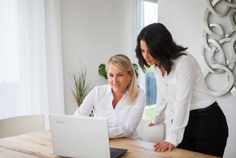 Kerstin sitzt im Termin zu einer Beratung mit Managerin vor dem PC und erklärt HR-Prozesse zum Beispiel Personalentwicklung