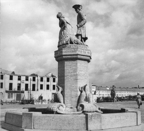 Aus dem Jahr 1954 stammt die Aufnahme, die die enttrümmerte Ruine des Rathauses samt Mudder-Schulten-Brunnen zeigt. Im Hintergrund Neubauten der Friedländer Straße.