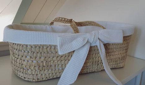 mozesmandje bekleed met witte wafelstof en voorzien van twee grote strikken. De bekleding is zo gemaakt dat deze er makkelijk afgehaald kan worden om te wassen. Bekleding voor mozesmandjes kan op afstand gemaakt worden en naar u toe gezonden worden.