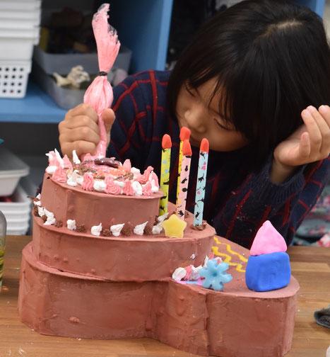 ケーキ本体が完成したらお待ちかねのデコレーションです。粘土で飾りをつくったり、これまた粘土クリームでつくったホイップをしぼりだしております。