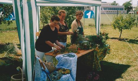 Drei Vereinsmitglieder zeigen, wie Blumenkränze gebunden werden.