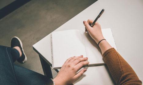 Hier sieht man das Bild einer Frau, die mit Stift und Papier schreibt.