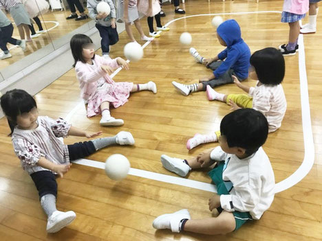 リトミックで、幼稚園児が二人組になって、ピアノに合わせたボール活動を行っています。