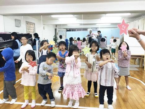 リトミックの活動で、幼稚園児が、数のついた星野プラカードを持って、ピアノに合わせてパフォーマンスの練習をしています。