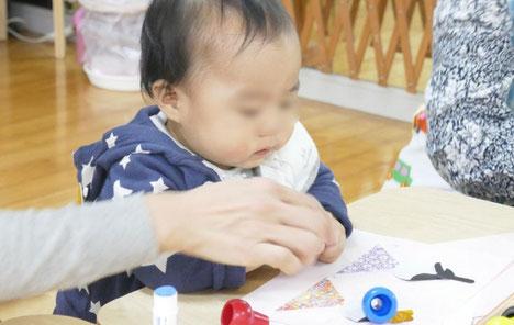 モンテッソーリの活動で、0歳児がお母様といっしょに雛人形を製作。お母様が作っているところに自分の手を添えて一生懸命に取り組んでいます。