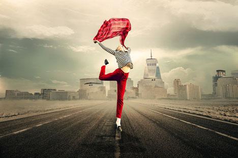 Sur une route goudronnée, une personne debout sur une jambe s'étirant vers le ciel en tenant une chemise colorée rouge entre ses bras tendus, sur fond de grande ville avec ses immeubles et une tour pointant sa flèche vers le ciel